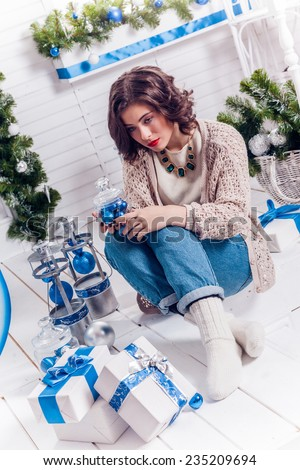 girl with Christmas gifts looking thoughtfully into the distance - stock photo