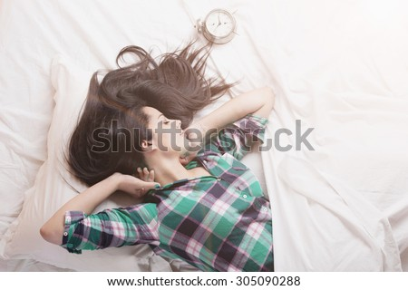Girl with clock waking up with bright sunflare  - stock photo