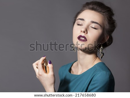 Girl with closed eyes holding a bottle of perfume - stock photo