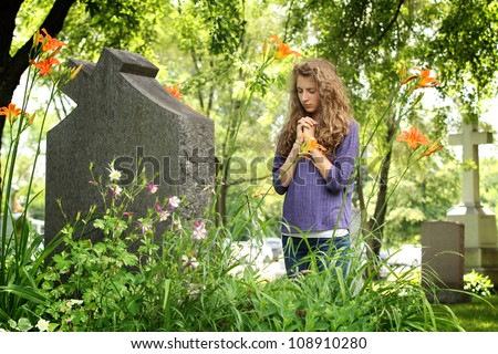 Girl with closed eyes pray in front of a tomb in a cemetery - stock photo