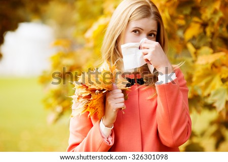 Girl with cold rhinitis on autumn background. Fall flu season. Ill sick sneezing woman. Handkerchief, vaccine against influenza virus Caught Cold Headache Allergy runny nose  - stock photo