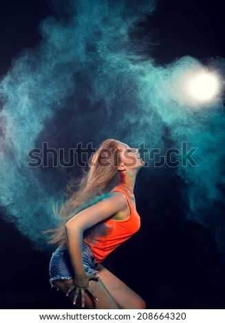 girl with colored powder trailing behind her hair that she is flinging up - stock photo