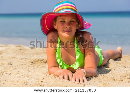 Girl with colorful hat lying on the beach - stock photo