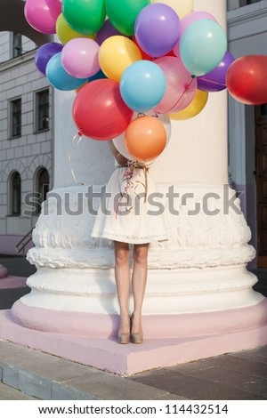 Girl with colorful latex balloons keeping her dress, urban scene, outdoors - stock photo