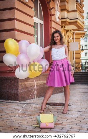 Girl with colorful latex balloons keeping her dress, urban scene, outdoors.