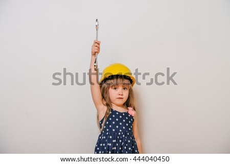 girl with construction tools. Little girl in polka-dot dress. little girl in a helmet. Child protection and safety. girl with construction tools. baby building. little girl making repairs. - stock photo