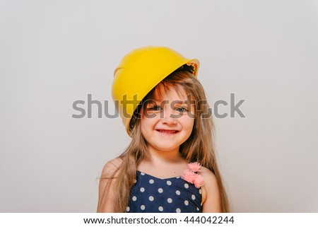 girl with construction tools. Little girl in polka-dot dress. little girl in a helmet. Child protection and safety.  baby building. little girl making repairs. little girl in a helmet laughing - stock photo