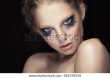 Girl with crying make up on black background in studio photo