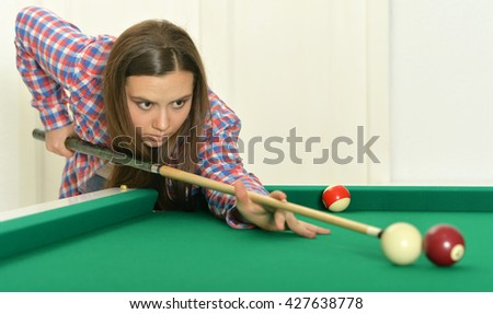 girl with cue playing billiard - stock photo