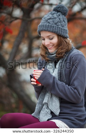 girl with cup in the autumn park.