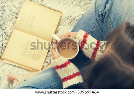 Girl with cup of coffee reading a book. Top view