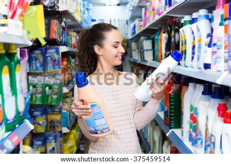Girl with curly hair selecting fabric conditioner in household store - stock photo