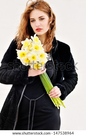 girl with daffodils in windy spring day - stock photo