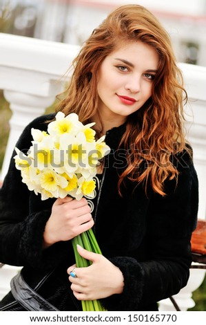girl with daffodils in windy spring day