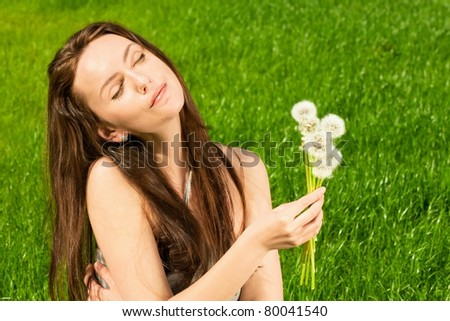 Girl with dandelions on green field