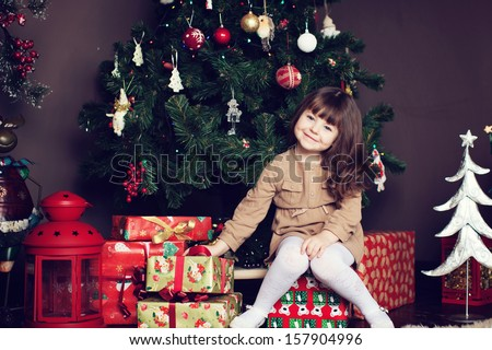 girl with dark hair sitting on a box with gifts. Christmas tree in the background. smiles