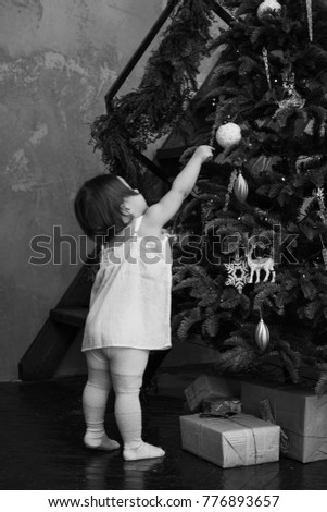 girl with dark hair standing near christmas tree