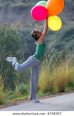 girl with different colored balloons jumping