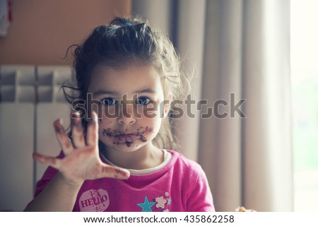 Girl with dirty mouth eating chocolate cookie - stock photo