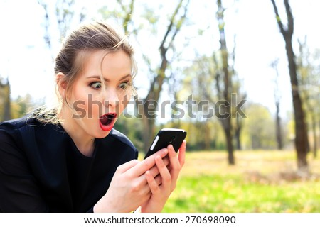 Girl with disheveled hair and open mouth stares into the smartphone - stock photo