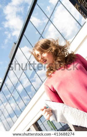 Girl with disheveled hair in the wind against the sky