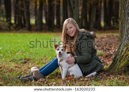 Girl with dog in autumn landscape