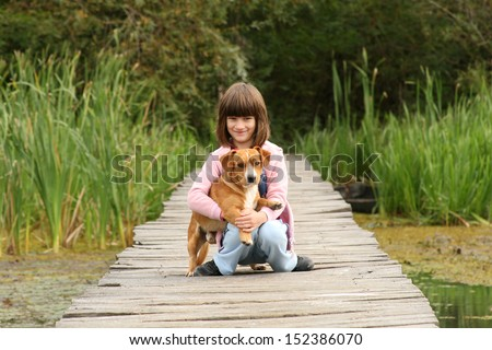 Girl with dog in her arms on wooden dock - stock photo