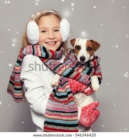Girl with dog in winter clothes. Happy child. Studio shot - stock photo