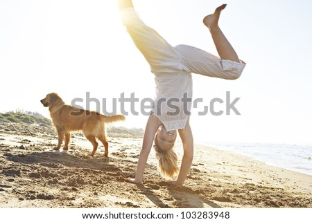 Girl with dog on the beach, doing cartwheels with the sun filtering through. - stock photo