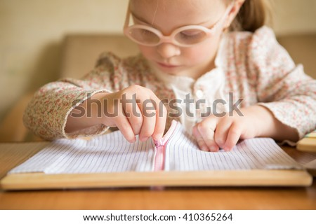 girl with Down syndrome learn to unzip clothes - stock photo