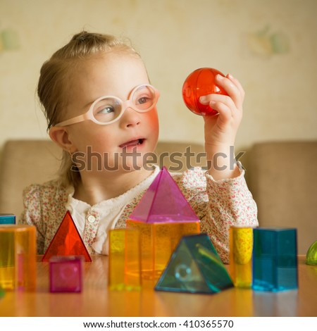Girl with Down syndrome playing with geometrical shapes - stock photo