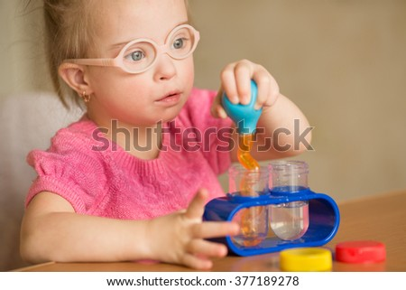 Girl with Down syndrome pours water by means of enema tubes in a test tube - stock photo