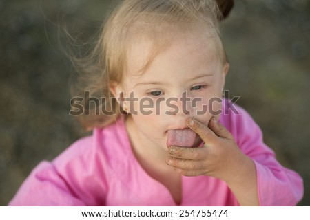 Girl with Down syndrome pulls his fingers in his mouth - stock photo