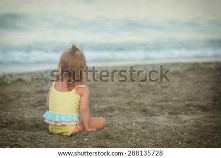 Girl with Down syndrome sitting on the beach - stock photo