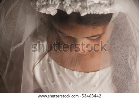 Girl with dressed up for her First Communion with a veil, soft focus - stock photo