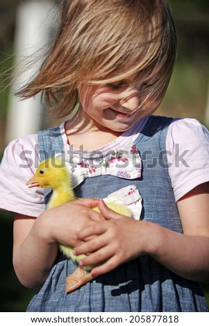 Girl with duckling on a farm