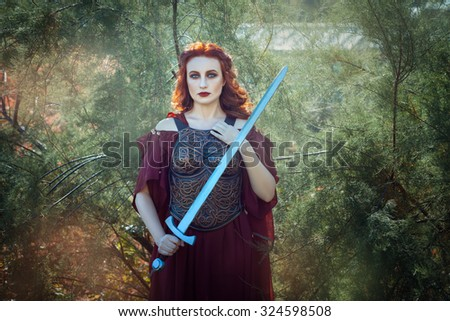 Girl with fiery hair warrior. In her hand she holds a sword. - stock photo