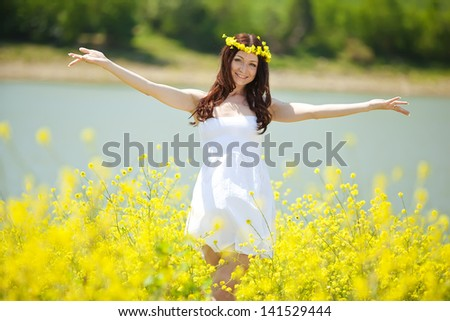 girl with flowers in the field - stock photo