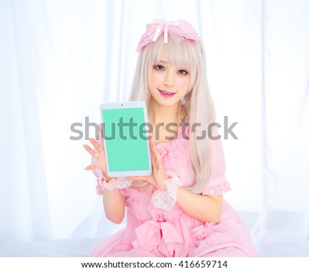 Girl with flowers pink lolita dress with a touch computer / japanese style - stock photo