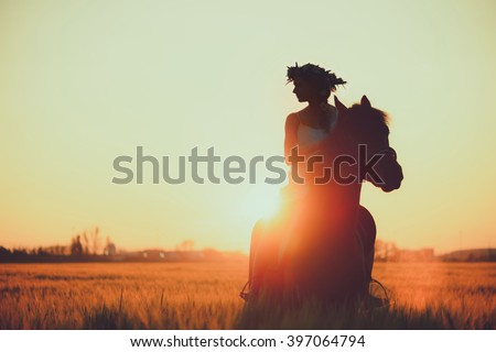 Girl with flowers wreathwhile riding horse at sunset  - stock photo