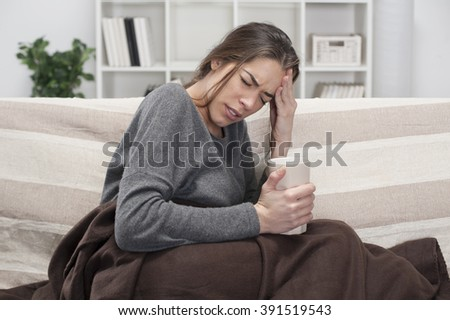 Girl with flu sitting on the bed in the room