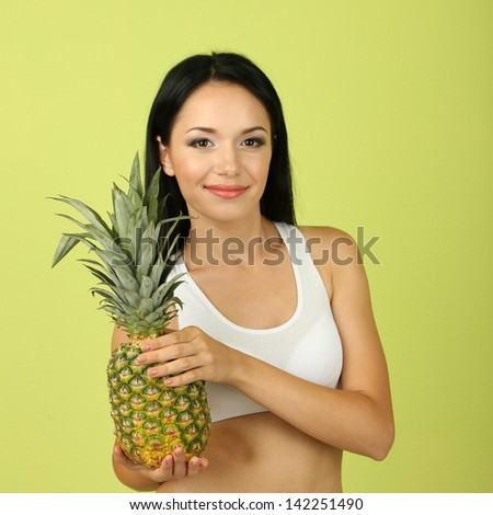 Girl with fresh pineapple on green background