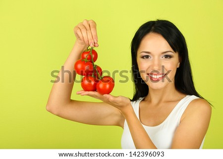 Girl with fresh tomatoes on green background