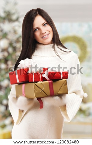 Girl with gift boxes near christmas tree.