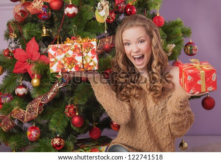Girl with gift boxes near christmas tree