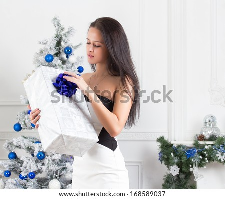 Girl with gifts near a Christmas tree
