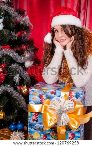 girl with gifts near a Christmas tree, long-awaited holiday, festive Christmas tree, happy face, festive attire.