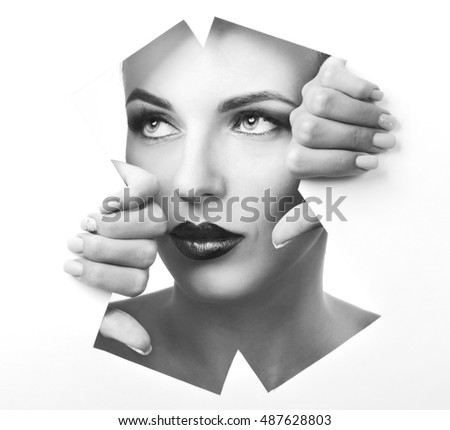 Girl with glamorous makeup looks through the geometric pattern in the paper