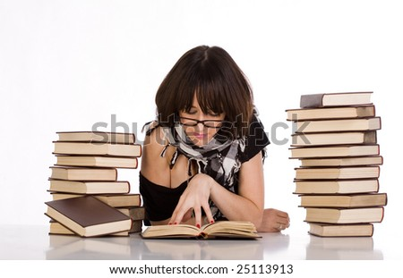 Girl with glasses learning and reading between two pile of books - stock photo