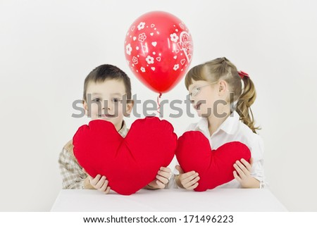 girl with glasses looks at the boy and smiles,best focus boy and heart,soft focus girls and balloon